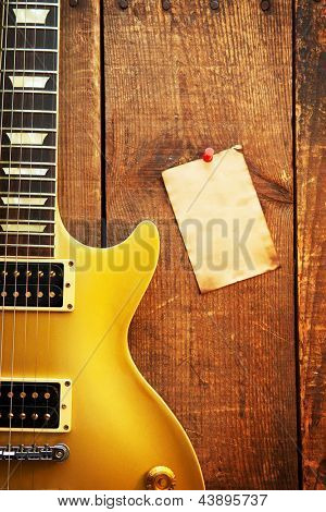 Vintage gold top single cutaway guitar on old wood surface and blank piece of paper, good for playlists, and production notes.