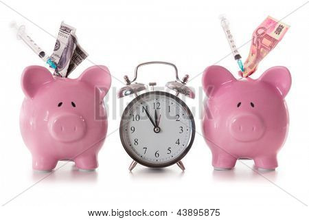 Dollar and euro notes and syringes sticking out of piggy banks with alarm clock on white background