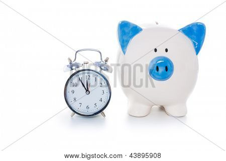 Hand painted blue and white piggy bank beside alarm clock on white background