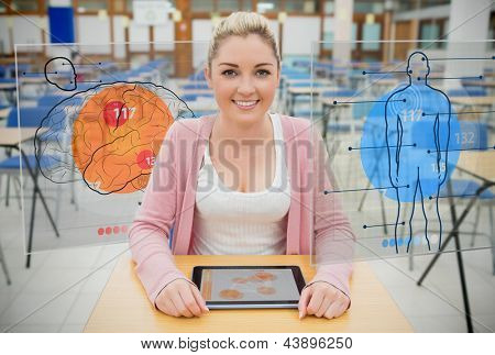 Front view of an attractive student with a tablet looking at futuristics interfaces