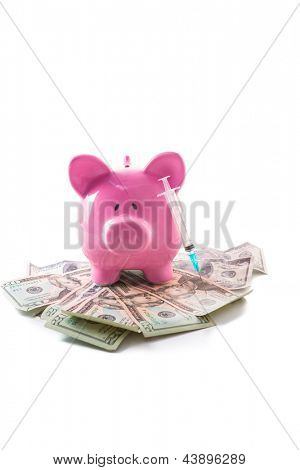 Piggy bank and syringe on a pile of dollars on white background