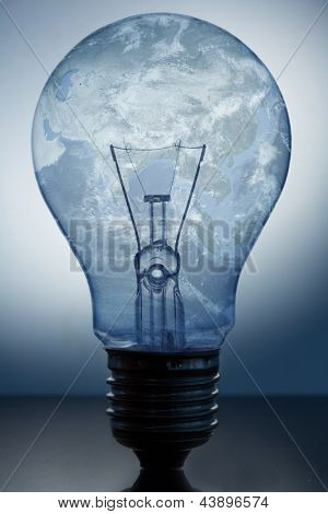 Close up of big light bulb standing with earths surface in it on reflective surface