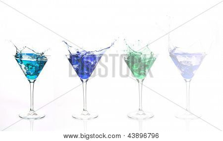 Serial arrangement of blue alcohol splashing in cocktail glass on white background