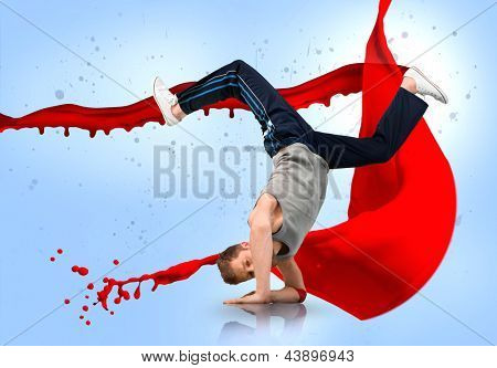 Break dancer balancing on his forearms with reflection below on red paint splash background