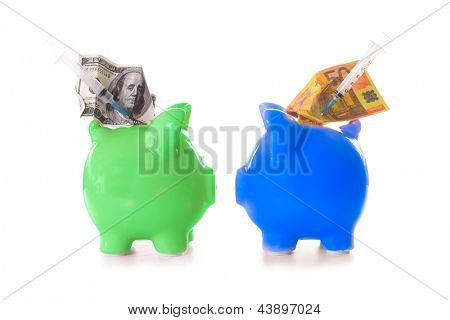 Dollar and euro notes and syringes sticking out of green and blue piggy banks