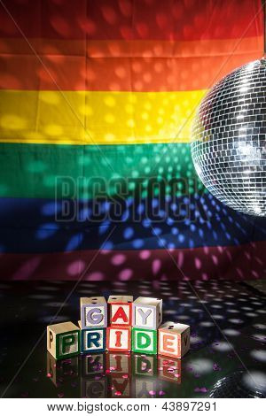 Blocks spelling out gay pride under light of disco ball with rainbow flag
