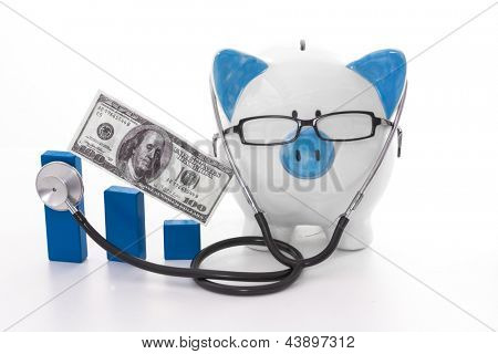 Blue and white piggy bank wearing glasses and stethoscope listening to graph model