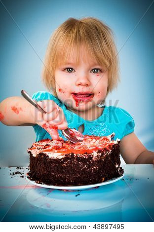 Little baby girl eating cake on a blue background