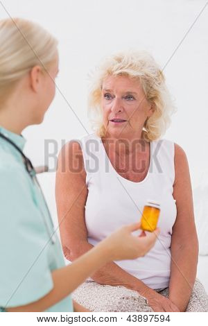 Doctor talking about a pill bottle to her patient at home