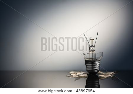 Shattered light bulb standing with copy space on reflective surface