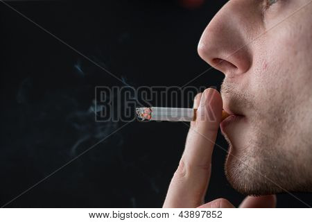 Man smoking cigarette on black background