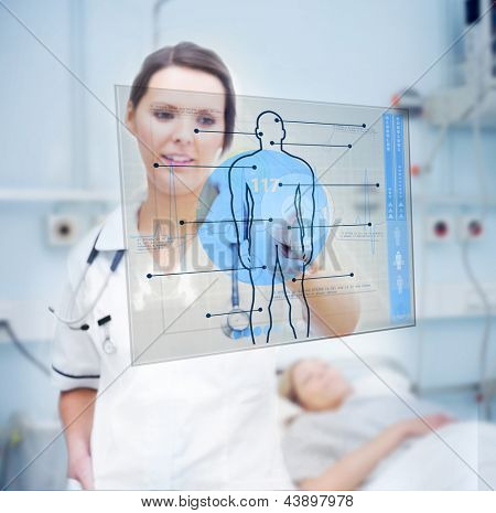 Nurse touching screen displaying blue human form in hospital ward