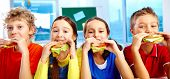 image of edible  - Four schoolkids looking at camera while having lunch during break - JPG