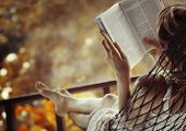 image of rest-in-peace  - Woman lying in a hammock in a garden and enjoying a book reading - JPG