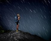 stock photo of meteoric rain  - Tourist with backpack standing on top of a mountain and enjoying night sky view with stars - JPG