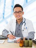 Постер, плакат: Молодые Юго Восточной Азии врач работает на его столе внутри комнаты больницы