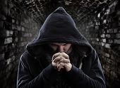 Постер, плакат: Отчаяние бандит молиться Богу о прощении