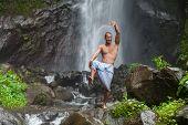 picture of qigong  - Young handsome man enjoying waterfall in the tropics - JPG