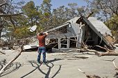 stock photo of grieving  - man grieving over house destroyed in flood - JPG