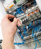 stock photo of fuse-box  - Hand of an electrician with screwdriver at an electrical switchgear cabinet - JPG