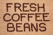 Coffee bean design in word form on a hessian background.
