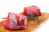 fresh red meat : two raw beef fillet chops on wooden board with small thyme twig ready to prepare .