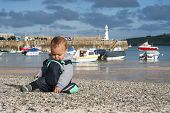 stock photo of st ives  - Toddler child boy on pebble seaside beach in the village port or harbour - JPG