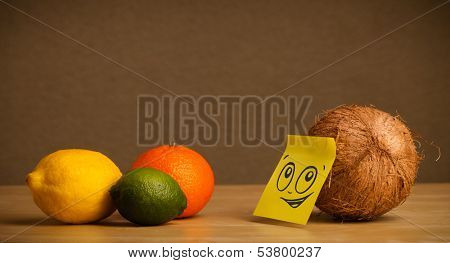Coconut with sticky post-it note reacting on citrus fruits