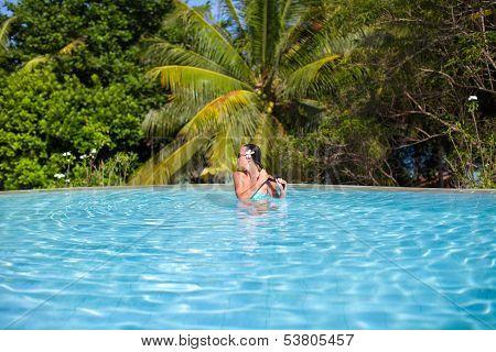Young Beautiful Woman Enjoying The Luxury Quiet Swimmingpool