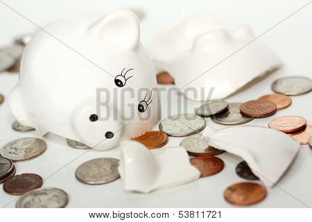 Broken Small Piggy Bank Surrounded By Spilled Coins