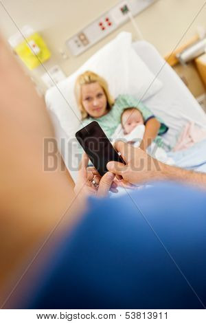 Man photographing woman and newborn babygirl through mobile phone in hospital