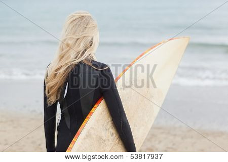 Rear view of a young woman in wet suit holding surfboard at beach