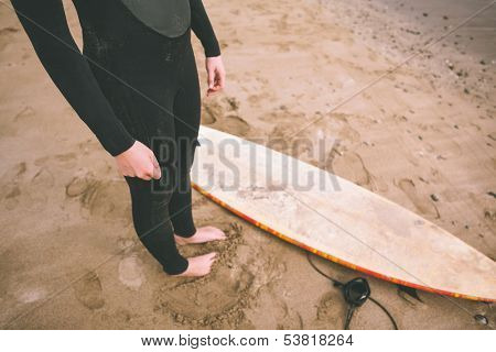 Low section of a young woman in wet suit with surfboard standing at the beach