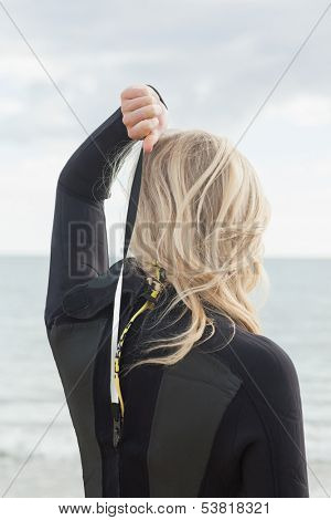 Rear view of a young blond in wet suit standing at the beach