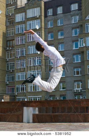 Men Jumping Against Urban Landscap