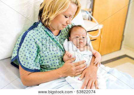 Loving mid adult woman looking at newborn baby girl while sitting on hospital bed