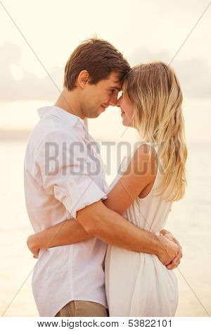 Happy romantic couple having loving moment touching foreheads looking into eachothers eyes. Man and woman in love on the beach at sunset