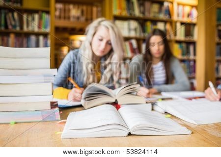 Two blurred students writing notes with stack of books at desk in the college library