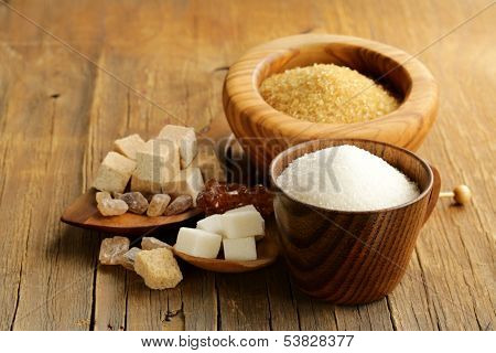 different kinds of sugar - brown, white, refined sugar on a wooden background
