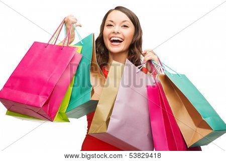 shopping, sale, gifts, christmas, x-mas concept - smiling woman in red dress with colorful shopping bags