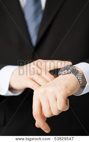 business people and office concept - close up of man looking at wristwatch