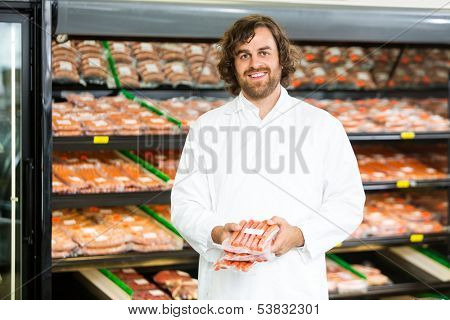 Portrait of happy salesman holding meat packages in butcher's shop