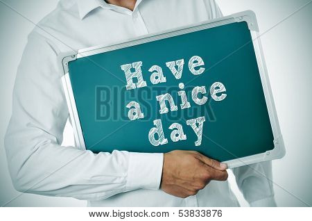man holding a chalkboard with the sentence have a nice day written in it