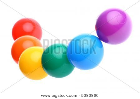 Six Shiny Coloured Plastic Toy Balls In Row Isolated On White. Copy Space And Room For Text Availabl