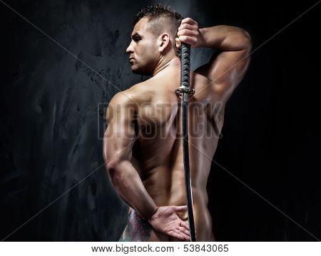 Attractive Muscular Man Posing Witf Sword.