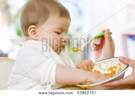 Close up of sweet messy baby boy playing with food in the bowl while eating.