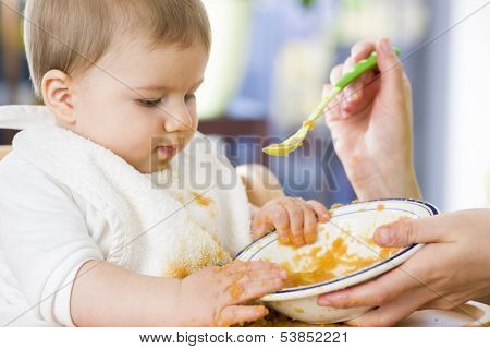 Close up of lovely messy baby boy playing with food in the bowl while eating.