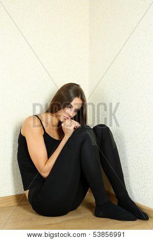 Lonely sad woman sitting on floor near wall