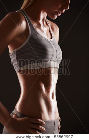 Body of slim female in activewear standing in isolation