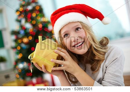 Portrait of happy girl holding giftbox and guessing what is inside on Christmas evening